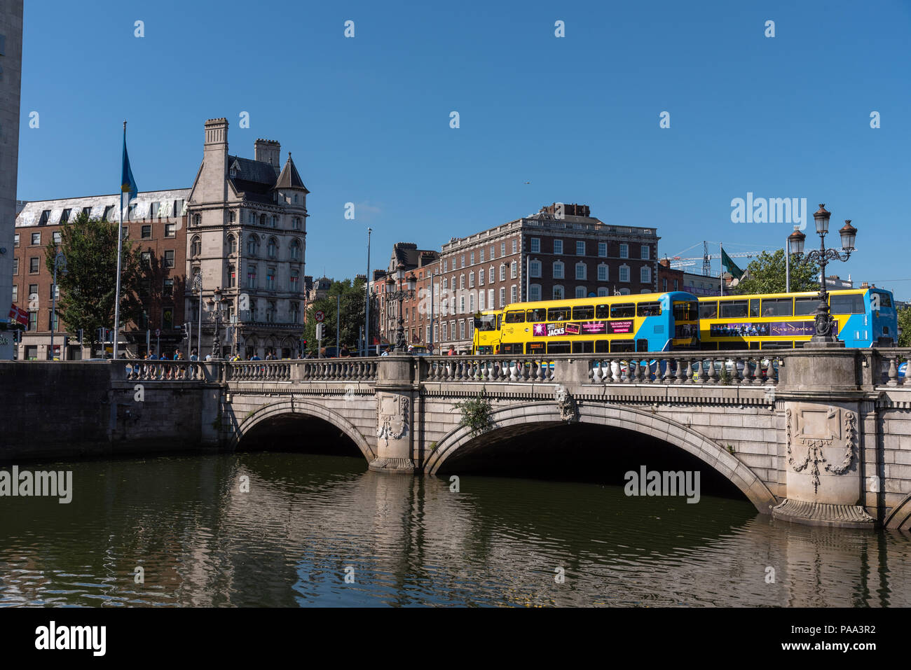 Tour busses cross a bridge over the River Liffey on a summer morning. - Stock Image