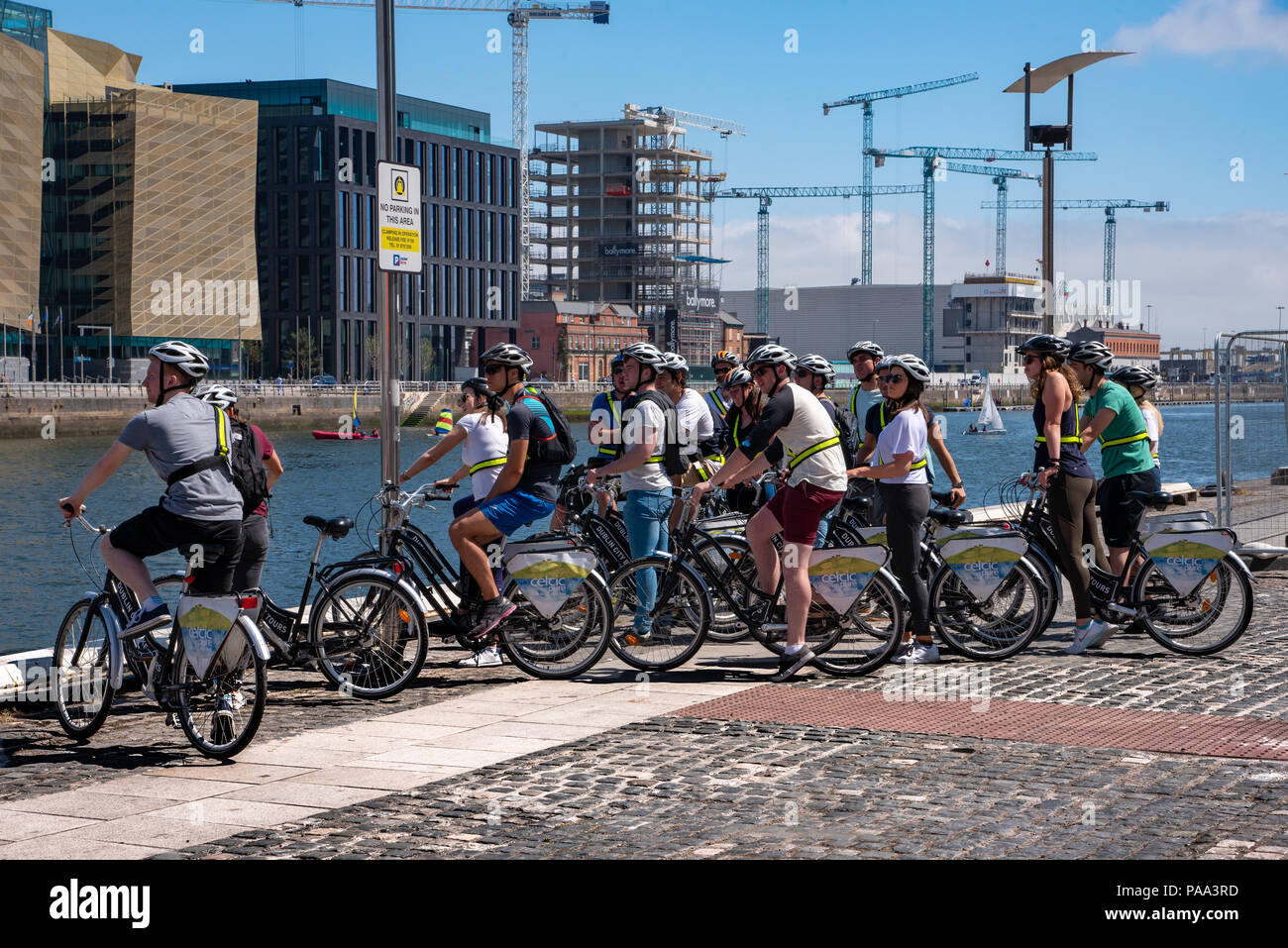 A group of tourists on bicycles is looking over the River Liffey in Dublin, Ireland. - Stock Image