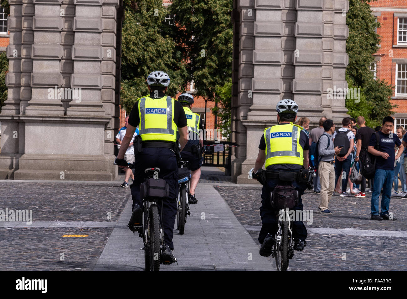 Guards from Trinity College enter a common area on bicycles. - Stock Image