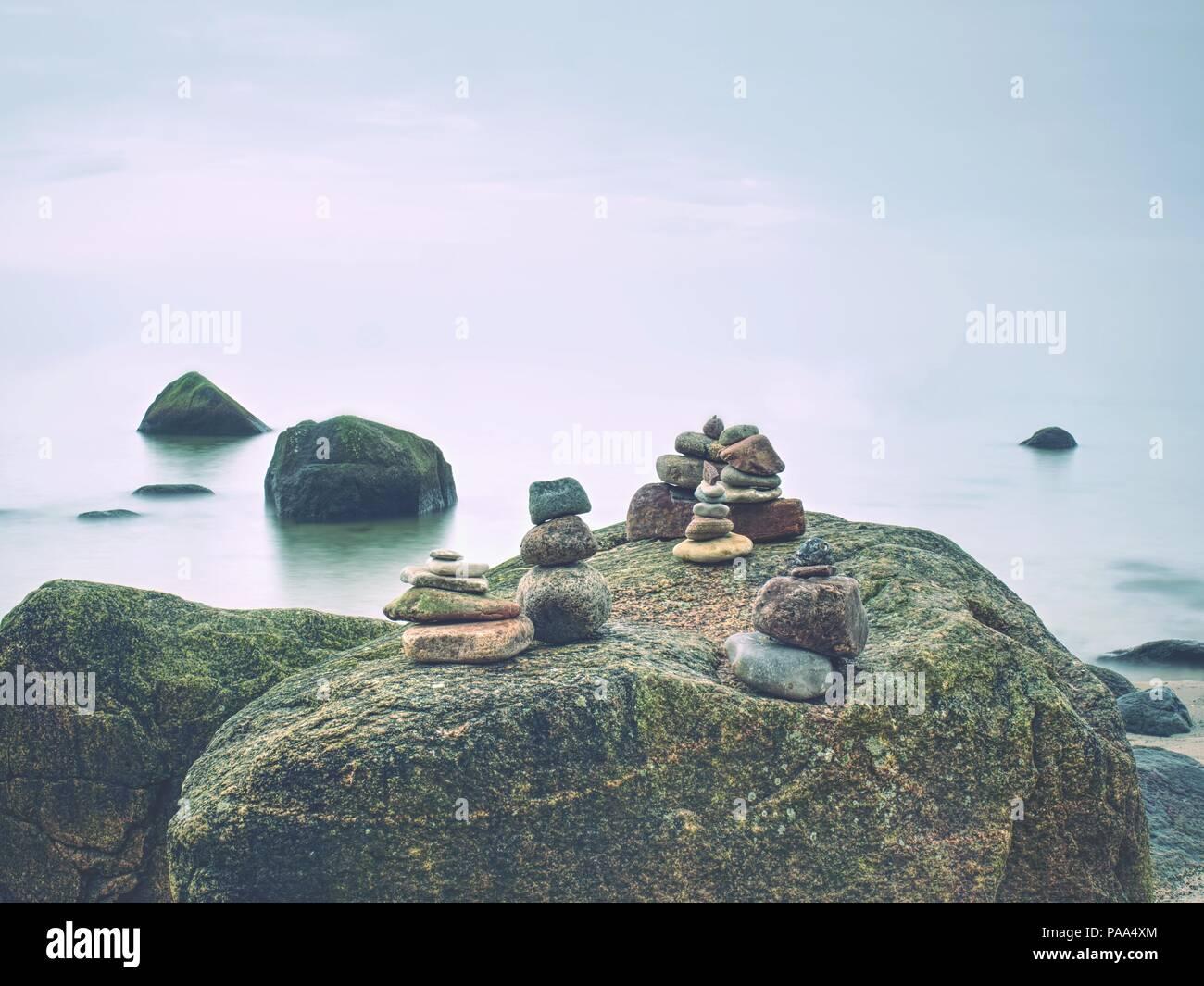 Stones pyramid symbolizing zen harmony balance pebbles. Peaceful ocean in background. Colorful flat stones for meditation. Stock Photo