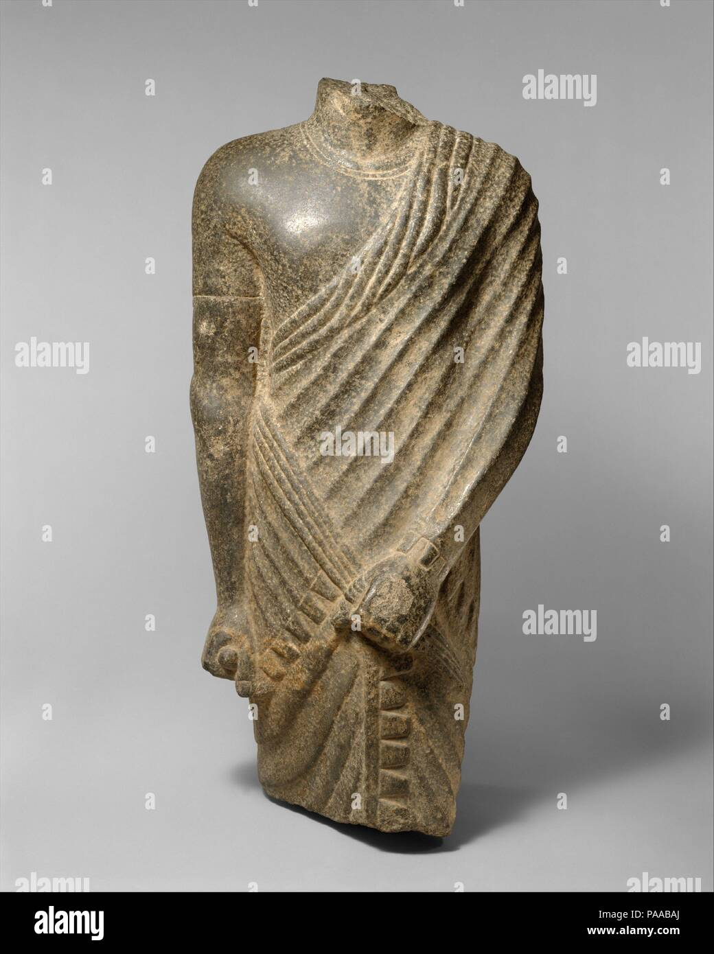 Torso of a Striding Draped Male Figure. Dimensions: H. 85 cm (33 7/16 in). Date: 304 B.C.-A.D. 364.  This statue wears a costume especially popular in the Ptolemaic and early Roman Period: a sleeved tunic over which a long fringed skirt is wrapped, with its front edge visible between the legs of the figure, topped with a fringed shawl.  The shawl covers the left arm and passes under the right, ending where it is gathered into the proper left fist. The sculptor has given special attention to the graceful ridges and hollows of the draped garment and to the fine anatomical modeling of the neck an - Stock Image