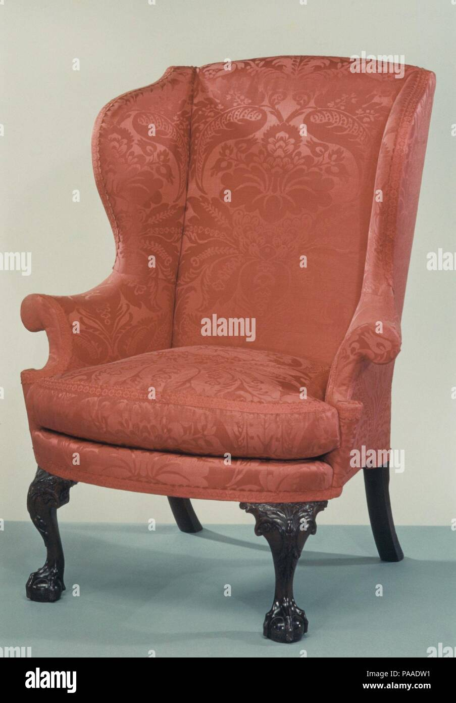Easy Chair. Culture: American. Dimensions: 46 x 37 x 28 1/4 in. (116.8 x 94 x 71.8 cm). Date: 1760-90.  In the eighteenth century, easy chairs (often called 'wing chairs' today) were usually found in bedrooms for the use of the aged or infirm. Thick padding and soft down cushions provided comfort, and the wings gave protection from drafts. This example, with its curved front seat rail and flared arms terminating in C-scrolls, exhibits the classic Philadelphia form. Museum: Metropolitan Museum of Art, New York, USA. - Stock Image