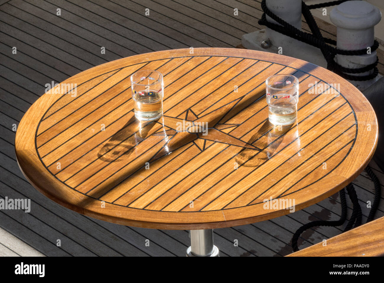 two wine gallses on a wooden outside table on a superyacht or boat. - Stock Image