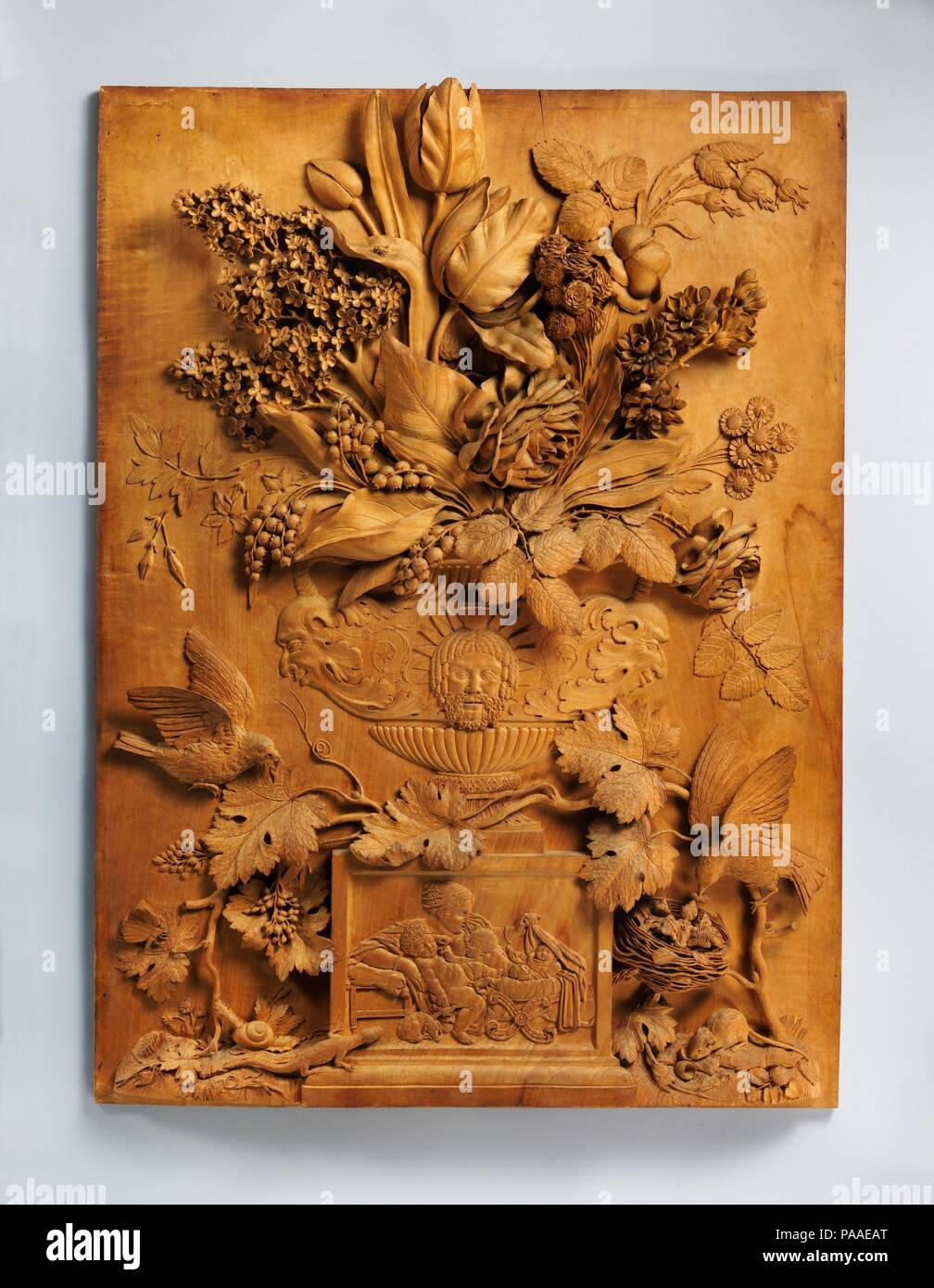 Floral still-life relief. Culture: French. Dimensions: Panel:  27 3/4 x 20 5/8 in.  (70.5 x 52.4 cm); Frame:  37 1/2 x 30 1/2 x 3 in. (95.3 x 77.5 x 7.6 cm). Maker: Aubert Henri Joseph Parent (French, Cambrai 1753-1835 Valenciennes). Date: 1784.  Carved of a single piece of soft lime wood, this high relief with its daring undercutting is an excellent example of the virtuoso work for which the French sculptor Aubert Parent was justly known. Reminiscent of Dutch seventeenth-century flower paintings, Parent's still lifes then as now drew admiration for their realism, delicacy, and the remarkable  - Stock Image