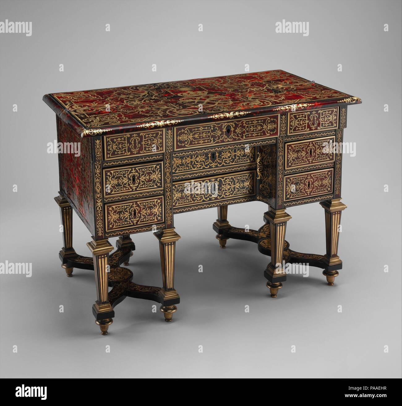 Small desk with folding top (bureau brisé). Culture: French, Paris. Designer: Designed and possibly engraved by Jean Berain (French, Saint-Mihiel 1640-1711 Paris) (1638/9-1711). Dimensions: 30 5/16 x 41 3/4 x 23 3/8 in. (77 x 106 x 59.4cm). Maker: Marquetry by Alexandre-Jean Oppenordt (Dutch, 1639-1715, active France). Date: ca. 1685.  With a folding top that lifts up to reveal a narrow writing surface, this desk is known in French as a bureau brisé ( literally, 'broken desk'). Introduced about 1669, this type of writing table remained fashionable until the early years of the eighteenth centur - Stock Image