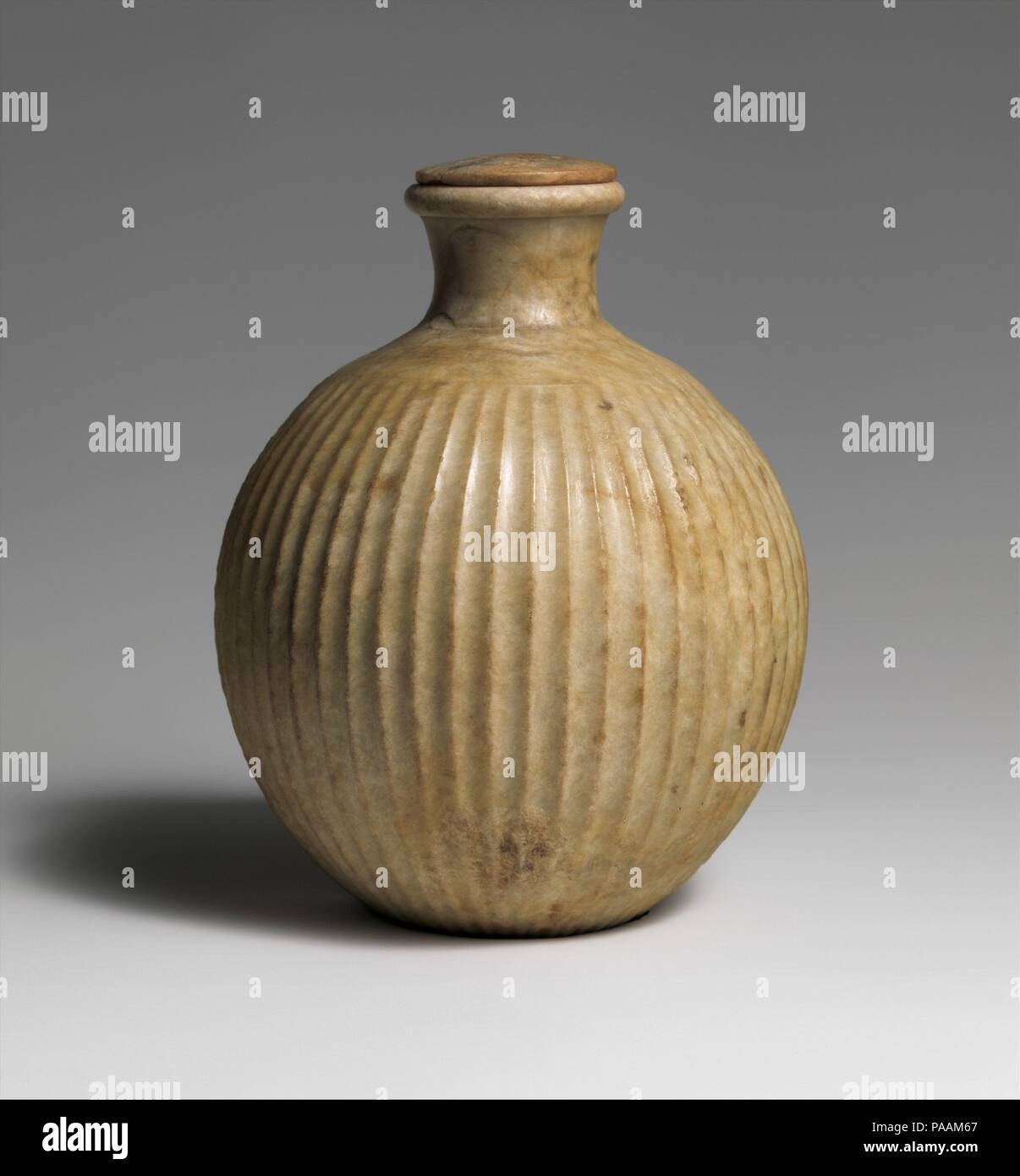Fluted bottle with lid. Dimensions: h. 1..5 cm (4 1/2 in). Dynasty: Dynasty 12. Date: ca. 1950 B.C.. Museum: Metropolitan Museum of Art, New York, USA. - Stock Image