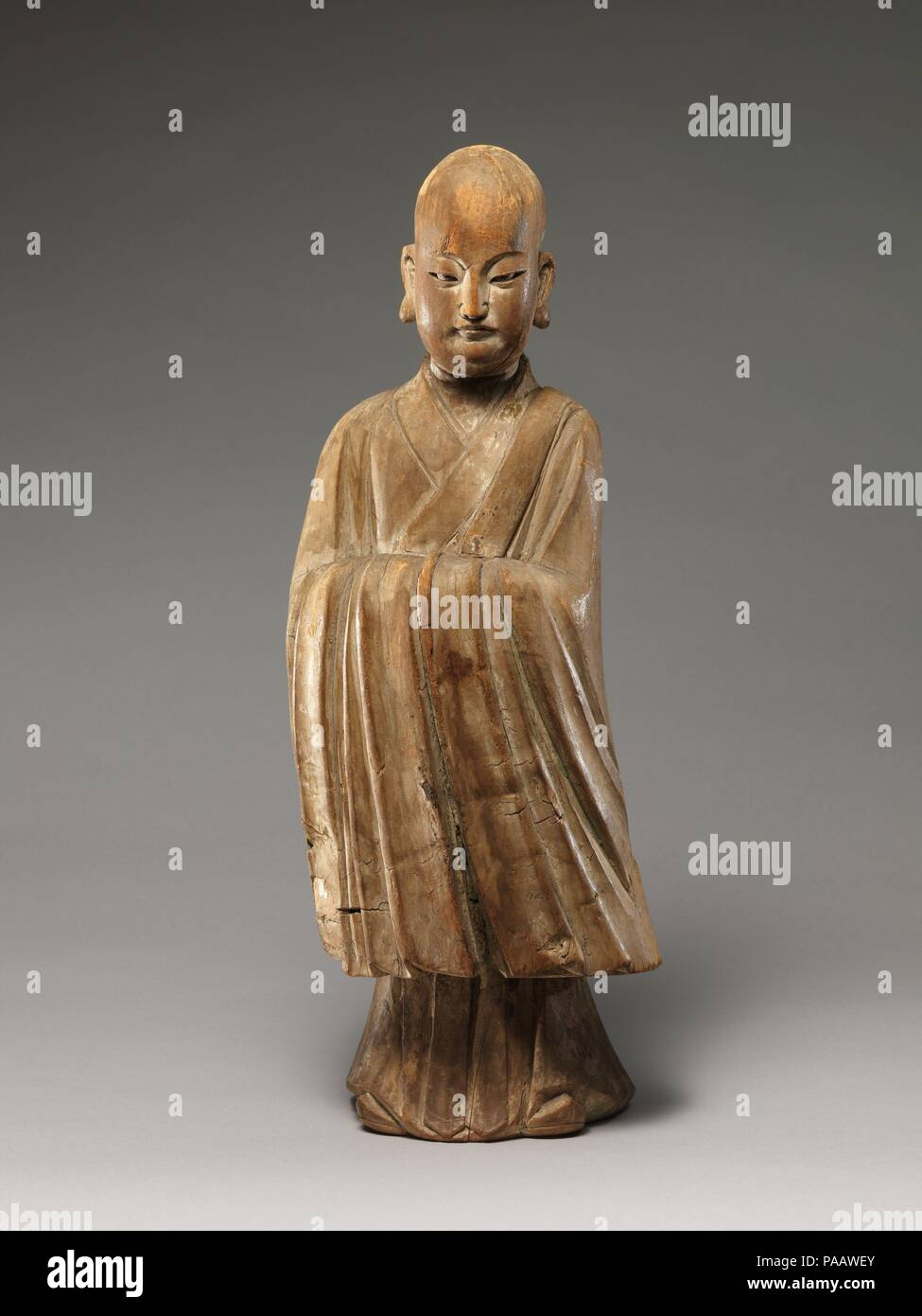 Arhat (Luohan). Culture: China. Dimensions: H. 19 1/8 in. (48.6 cm); W. 7 in. (17.8 cm). Date: 16th-17th century.  This sculpture epitomizes the merging of religious and secular imagery in later Chinese Buddhist sculpture. With his shaven head and elongated earlobes, the figure resembles a luohan (one of the Indian disciples of the Buddha), but his refined facial features, dignified posture, long-sleeved robe, and pointed shoes--all attributes associated with Confucian scholar-officials--identify him unmistakably as a youthful monk.  The sculpture's tendency toward abstraction and stylization- - Stock Image