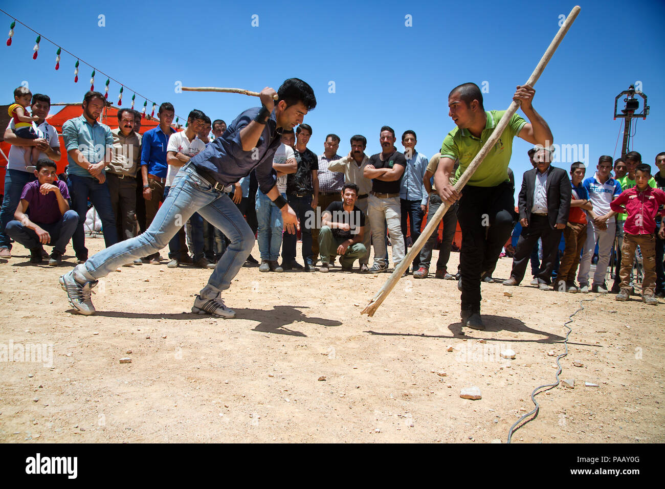 Young Qashqai men fighting with sticks during a traditional stick fight and wedding ceremony,  nomad people, Iran - Stock Image