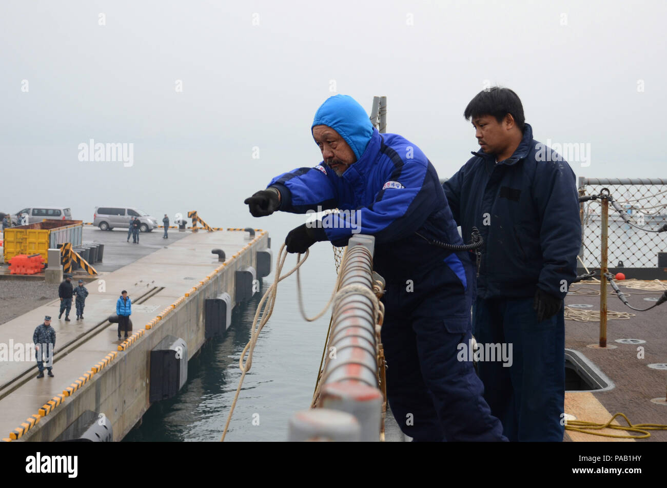 160304-N-WJ640-032 GWANGYANG, South Korea—Civilian mariner Robert Cheong (left) and civilian mariner Rejinan Barque communicate with pier side sailors to tie mooring lines on board dry cargo/ammunition ship USNS Sacagawea (T-AKE 2) here, March 4. The Sacagawea was one of three MPF ships that offloaded her cargo in support of Exercise Ssang Yong 16 (SY16), under the Exercise Freedom Banner 2016 (FB16) directive. Freedom Banner 2016, a Navy and Marine Corps deployment and offload/backload exercise that is nestled within SY16, brought multiple commands together to offload Maritime Prepositioning  Stock Photo