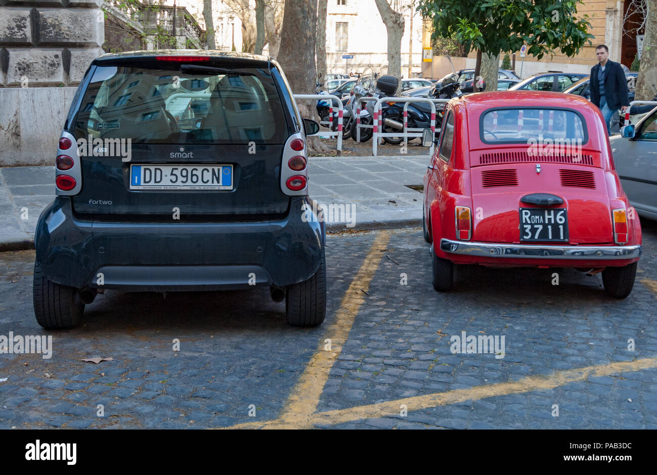 How our concept of small has changed over 40 years. An original Fiat Cinquecento beside a Smart fortwo car in a Rome side street. - Stock Image