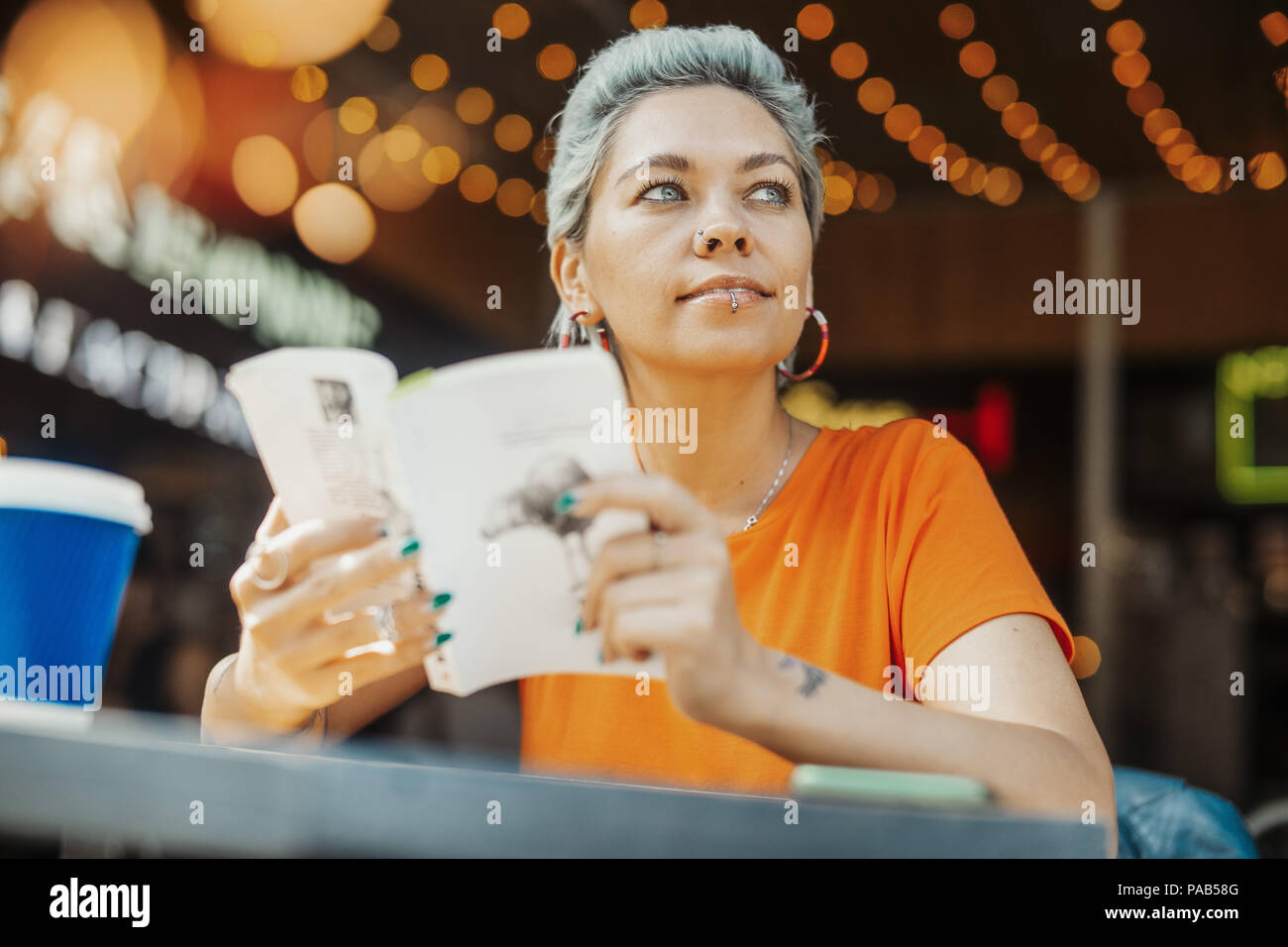 Attractive blonde girl reading book at cafe - Stock Image