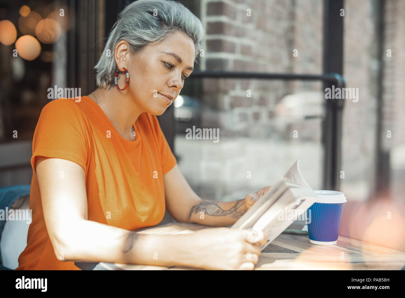 Attractive tattooed blonde girl reading book - Stock Image