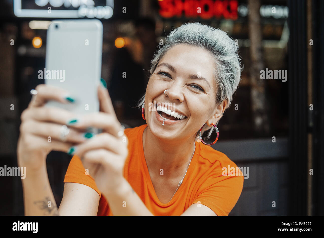 Attractive positive blonde woman in orange T-shirt making selfie at cafe - Stock Image