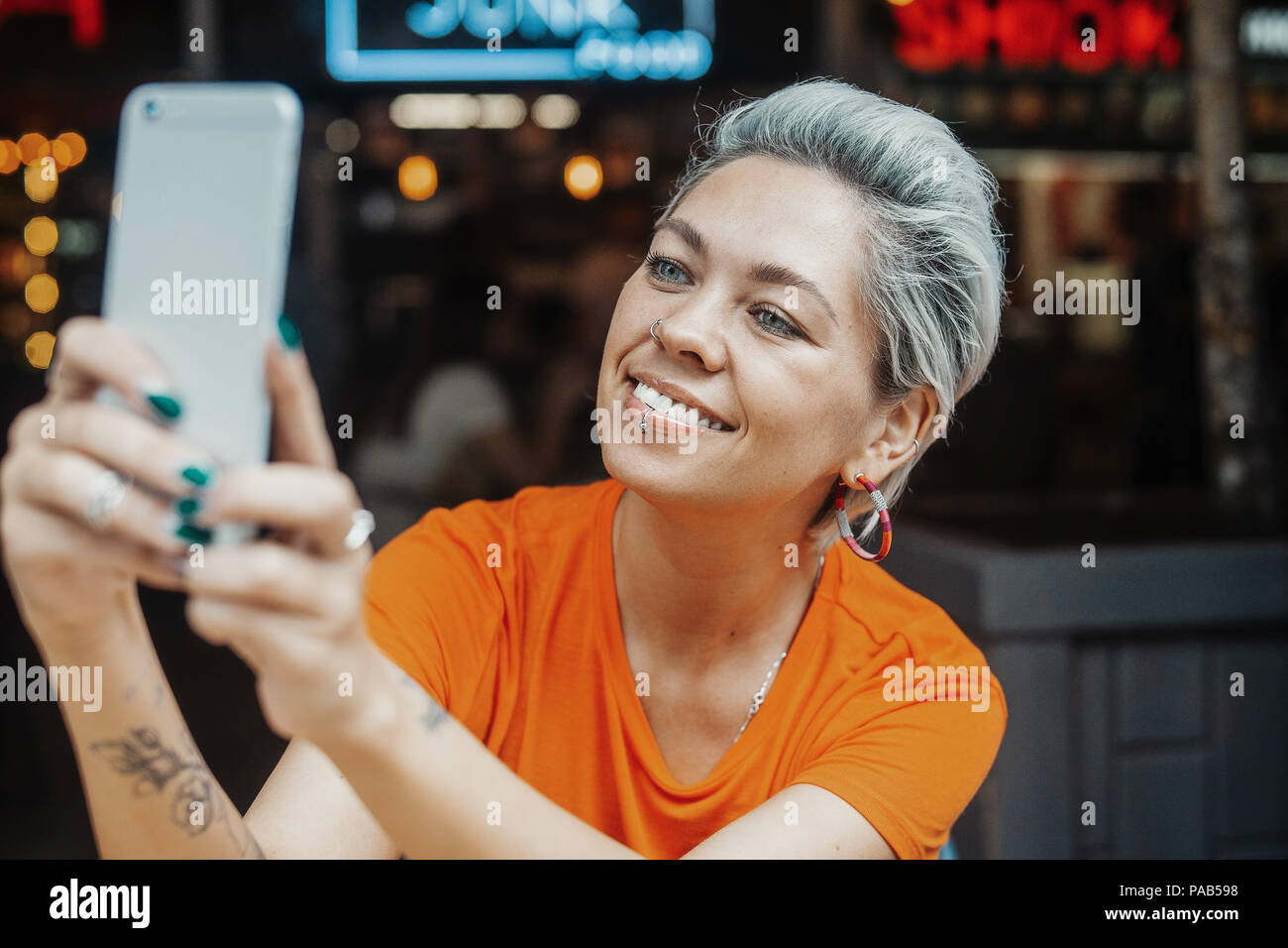 Close up of attractive blonde girl in orange T-shirt making selfie at cafe - Stock Image