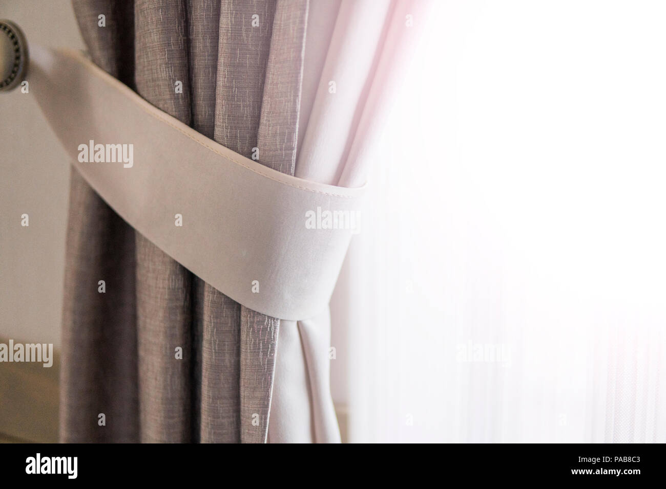 Curtain against window with a warm sunlight. - Stock Image