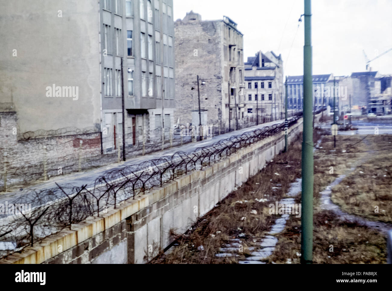 1960s view of Berlin Wall, West Germany,looking into East Germany, GDR, through barbed wire. Digital conversion of slide taken in 1964. - Stock Image