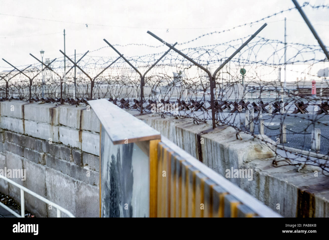 1960s view of Berlin Wall, West Germany, looking into East Germany, GDR, through barbed wire with Czech hedgehog barriers. Digital conversion of slide taken in 1964 - Stock Image