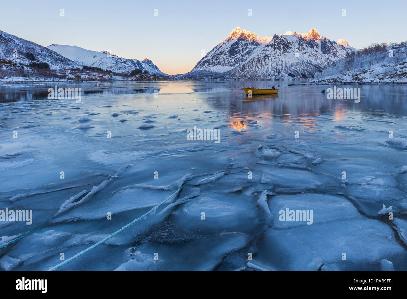 Winter scene of boat in partially frozen fjord and snowy landscape. Blue ice and water cast reflections of mountain peaks in orange sunset. - Stock Image