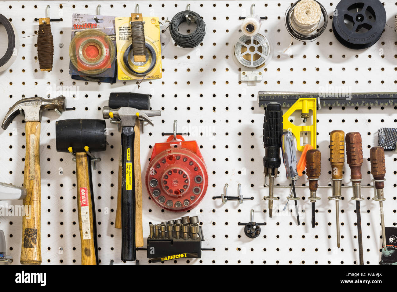 Assorted tools hanging on pegboard - Stock Image
