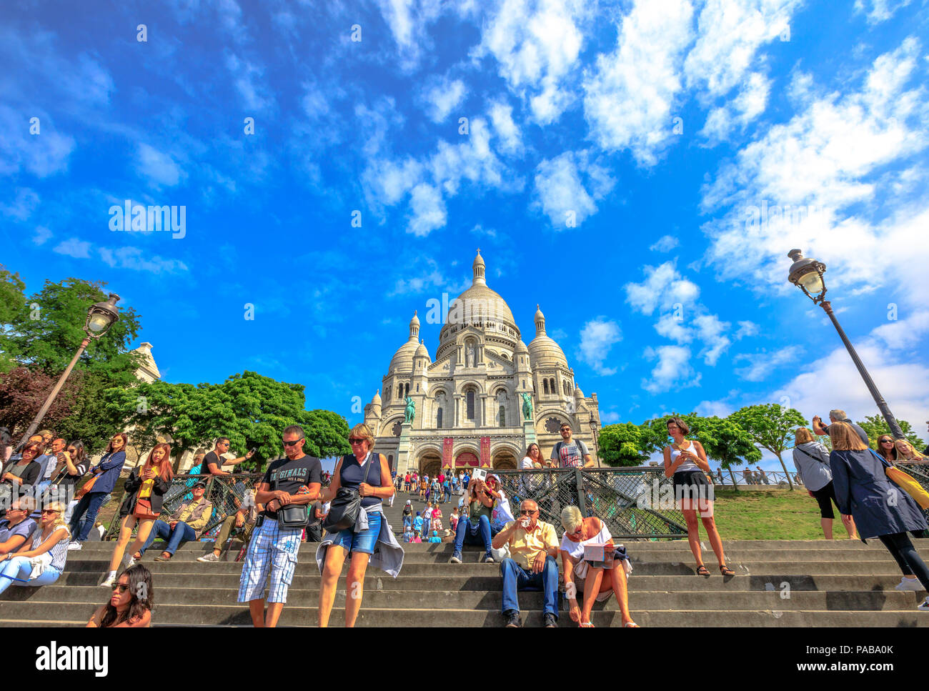 Paris, France - July 3, 2017: many people on the stairs of Basilica of Sacre Coeur de Montmartre in Paris in a sunny day with blue sky. Sacred Heart Church is a popular tourist landmark. Bottom view. - Stock Image