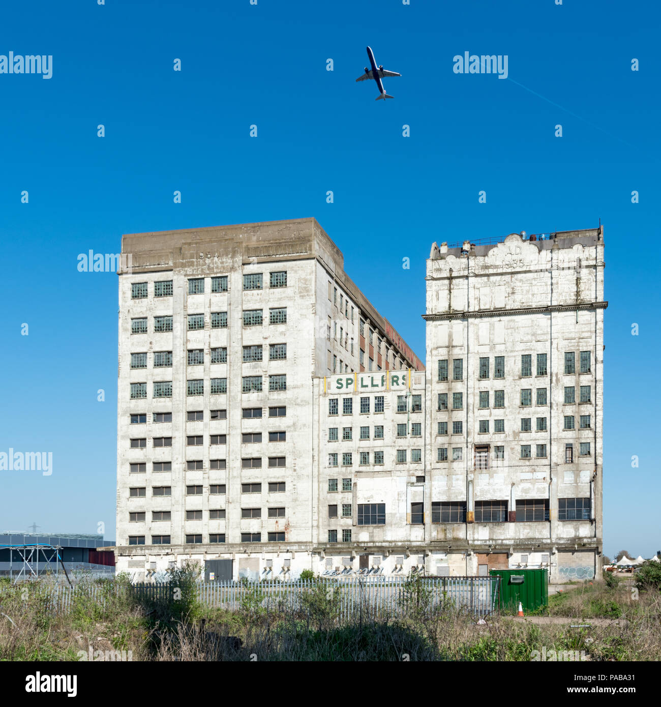 Aircraft soaring over the Spillers Millennium Mills in West Silvertown one on its departure from London City Airport - Stock Image