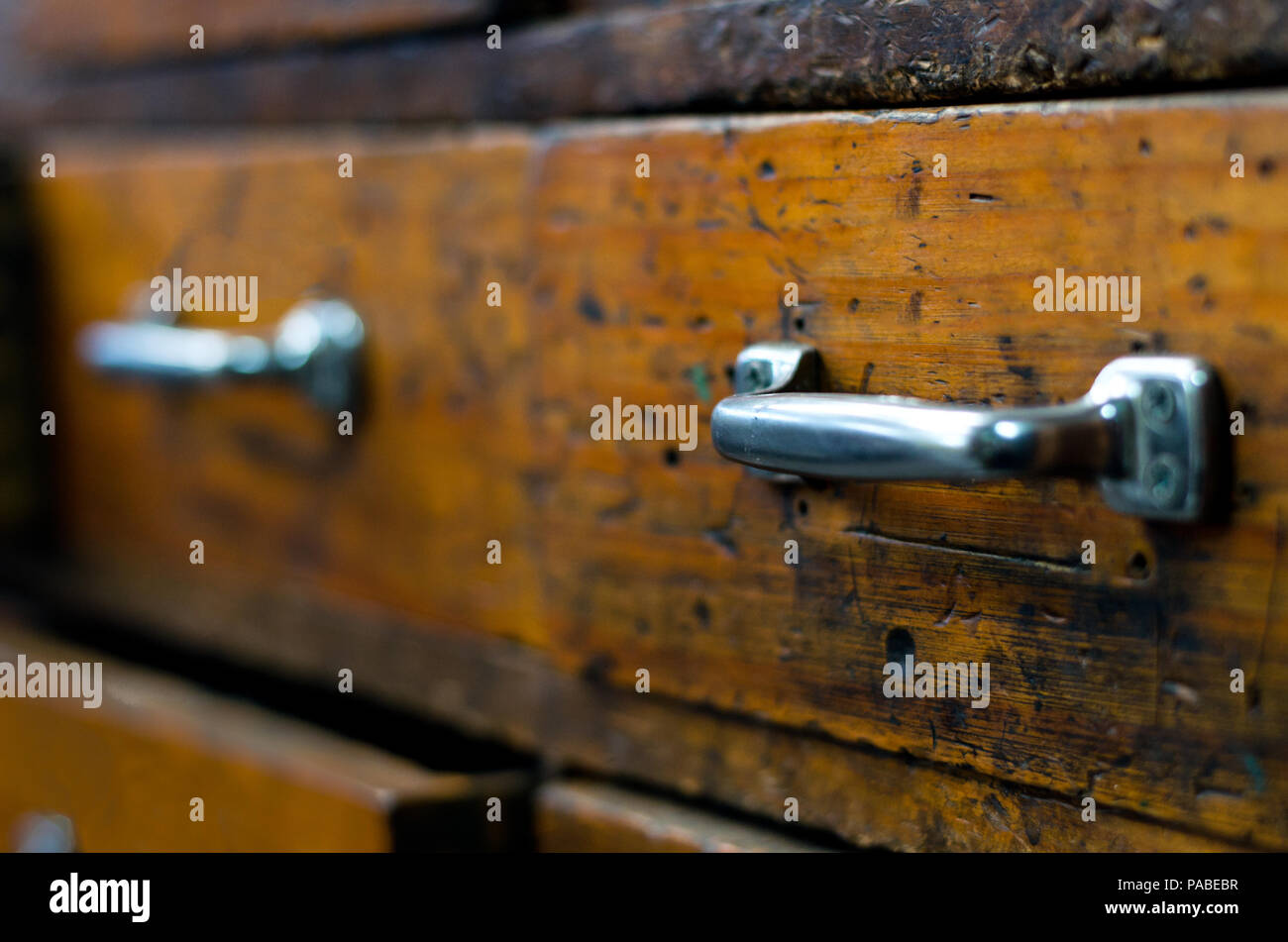 Close up of two wooden drawers with chrome handles, focussing on the handle of the closest drawer. - Stock Image