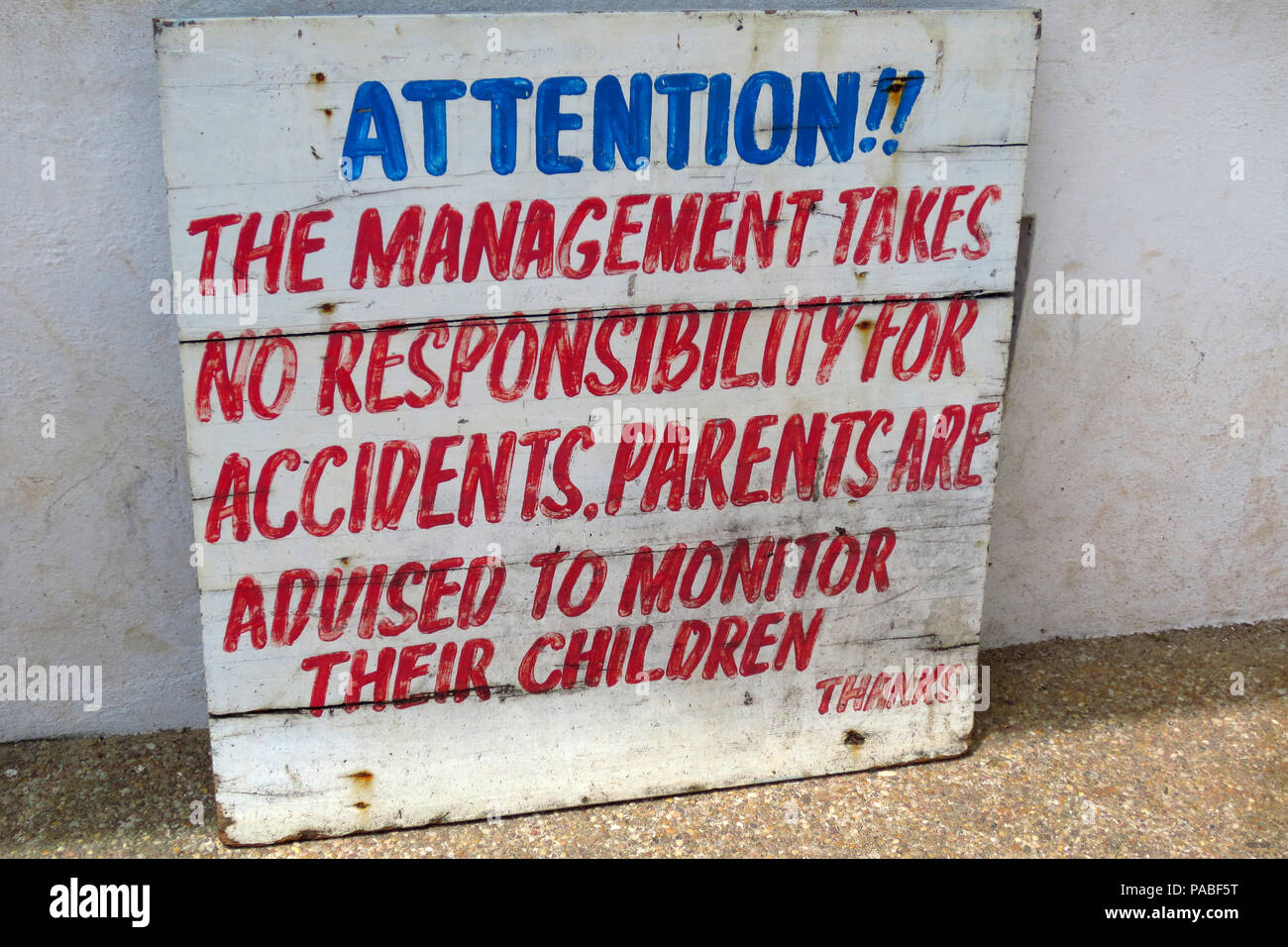 Handwritten legal disclaimer sign at the entrance of a crocodile farm in Cape Coast, Ghana - Stock Image