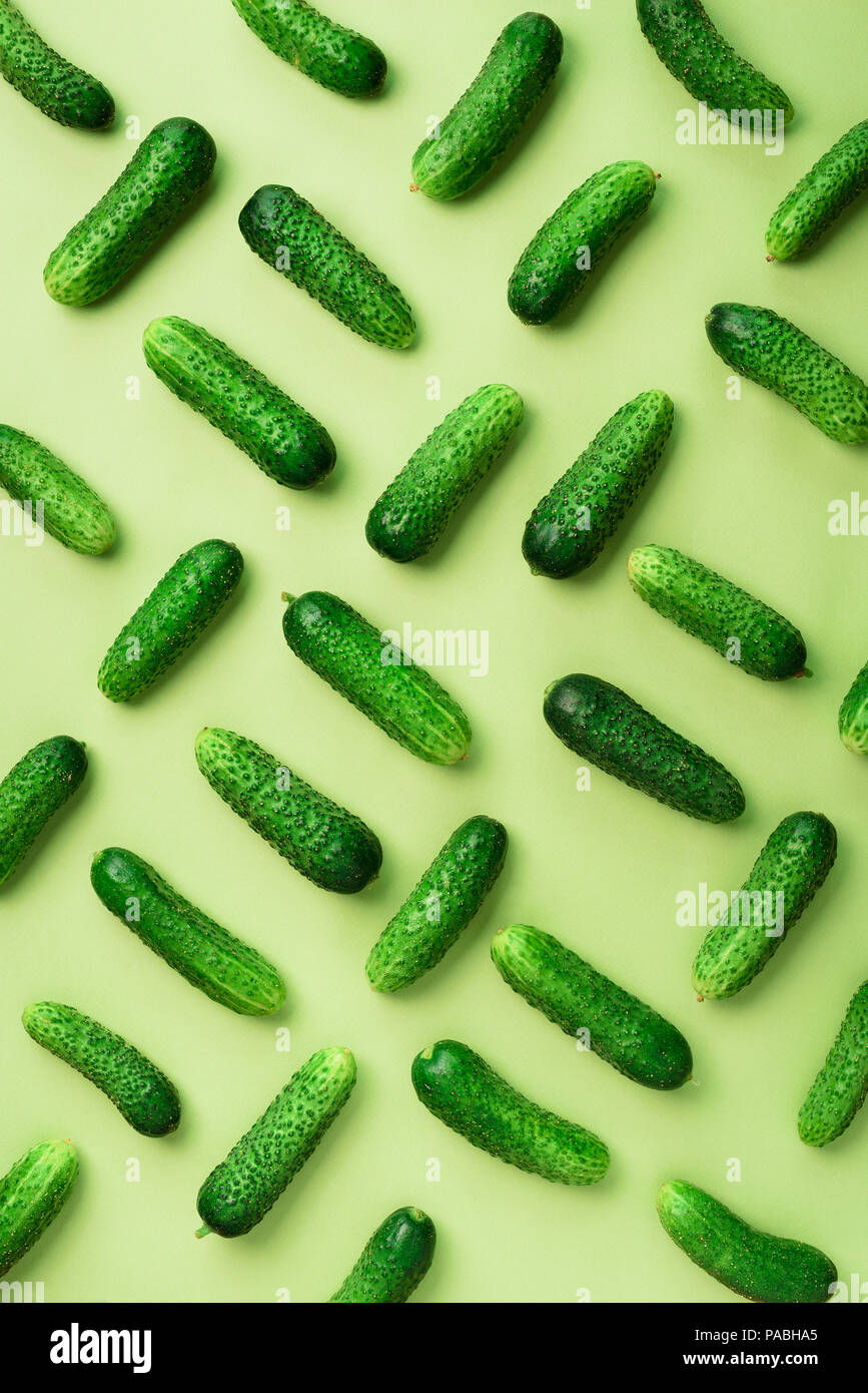 Creative pattern of fresh cucumbers on green background. Top view. Copy space. Minimal design. Vegetarian, vegan, organic food and alkaline meal conce - Stock Image
