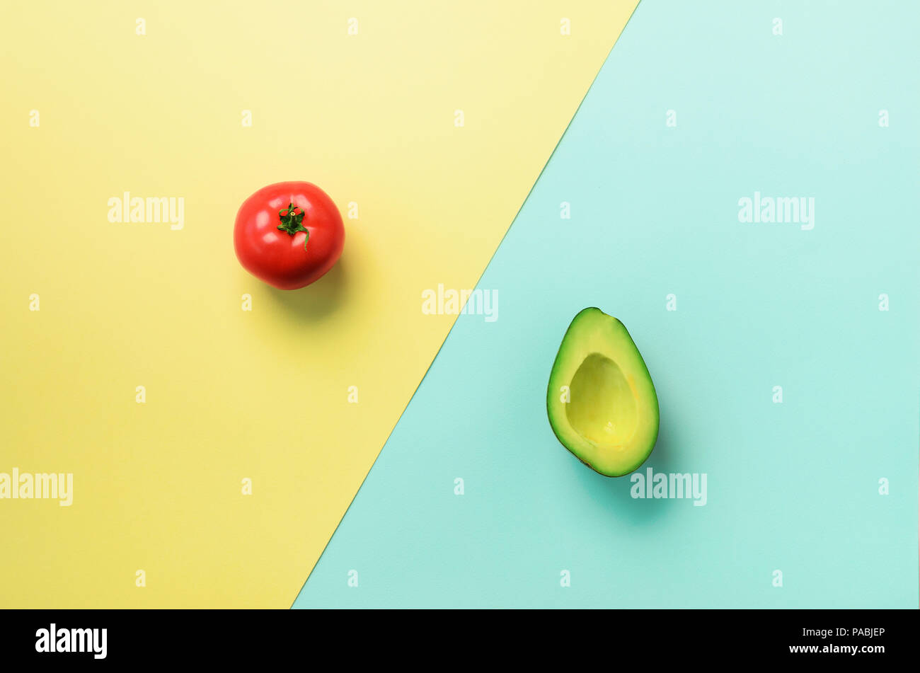 Green sliced avocado and red tomato on blue and yellow background. Top view. Pop art design, creative summer food concept. Minimal flat lay style Stock Photo