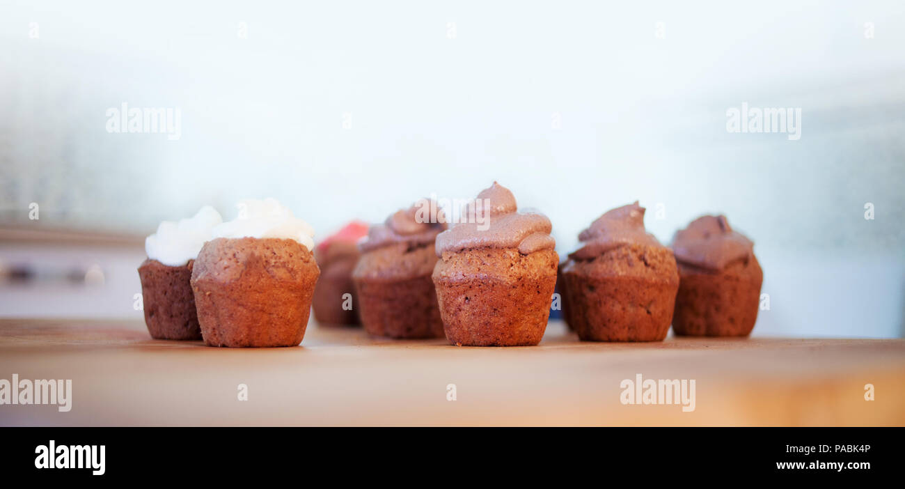 Chocolate muffins on the desk. Cupcakes with different creams. Copy space on the top - Stock Image
