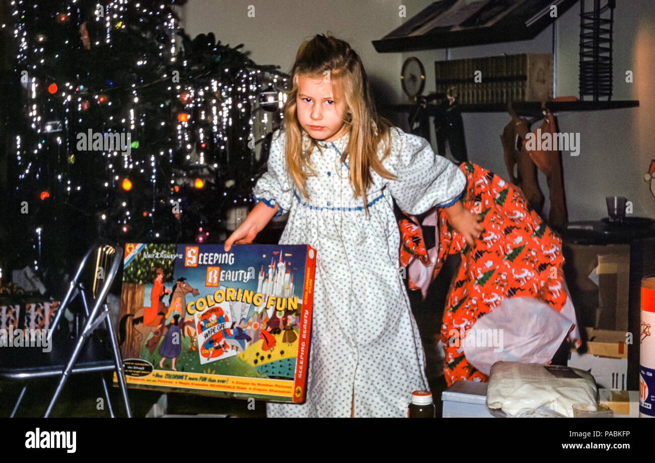 1960s young girl with long blonde hair wearing a nightdress looking tired, unwrapping a Christmas present in front of Christmas tree in family living room on Christmas morning. The wrapping paper is being tossed aside.  The Christmas present is a large box labelled 'Sleeping Beauty Coloring Fun'. Digital conversion of historical photo taken in USA in 1960 - Stock Image