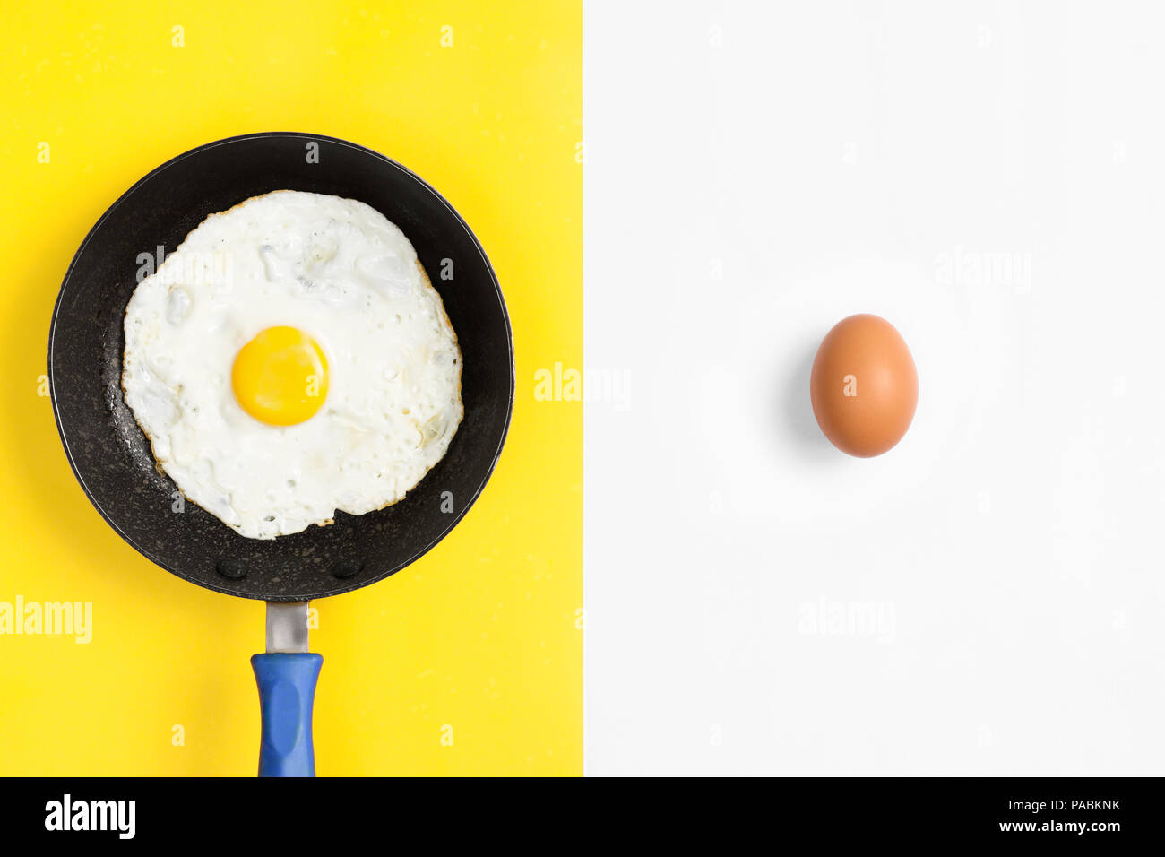 Split color flat lay image with cooked and uncooked egg. - Stock Image