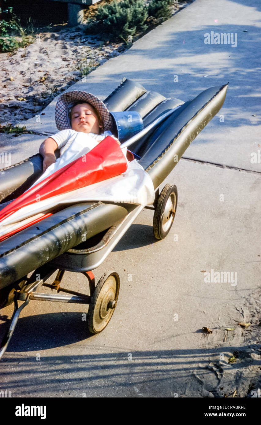 1950s baby boy asleep in beach wagon with plastic inflatable lilo and beach umbrella, Breezy Point, Long Island, Queens, New York City, USA. Digital conversion of historical photo taken in 1959 - Stock Image