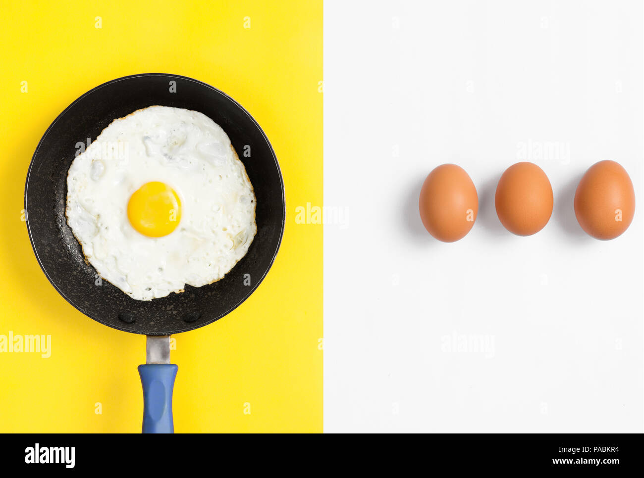 Split color flat lay image with cooked egg in a a pan and uncooked eggs lined up. - Stock Image