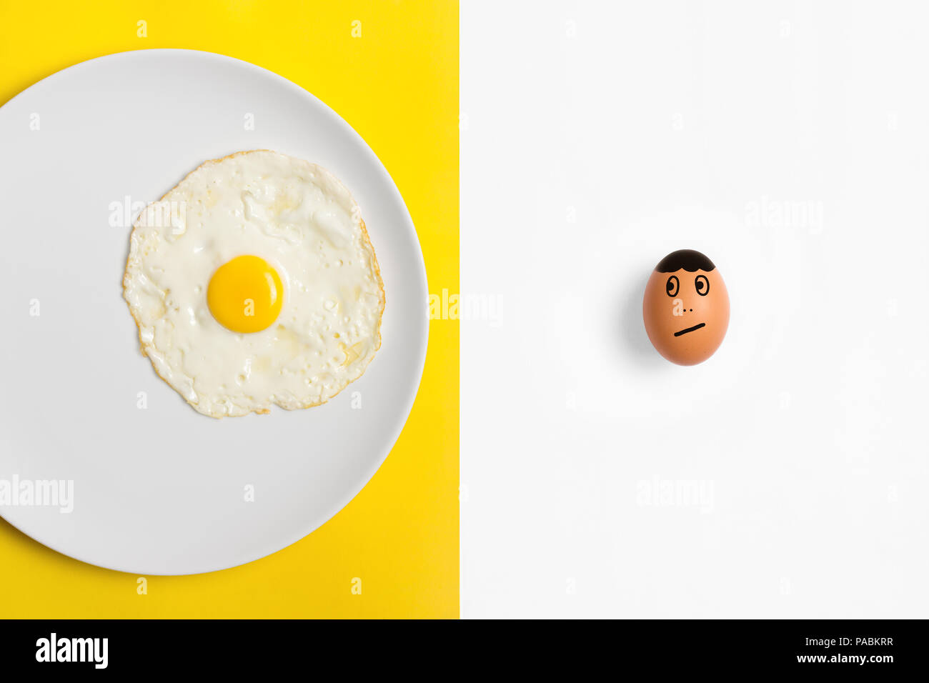 Fried egg on plate with  an uncooked egg  looking worried he's next. Two tone split color background flat lay image. Stock Photo