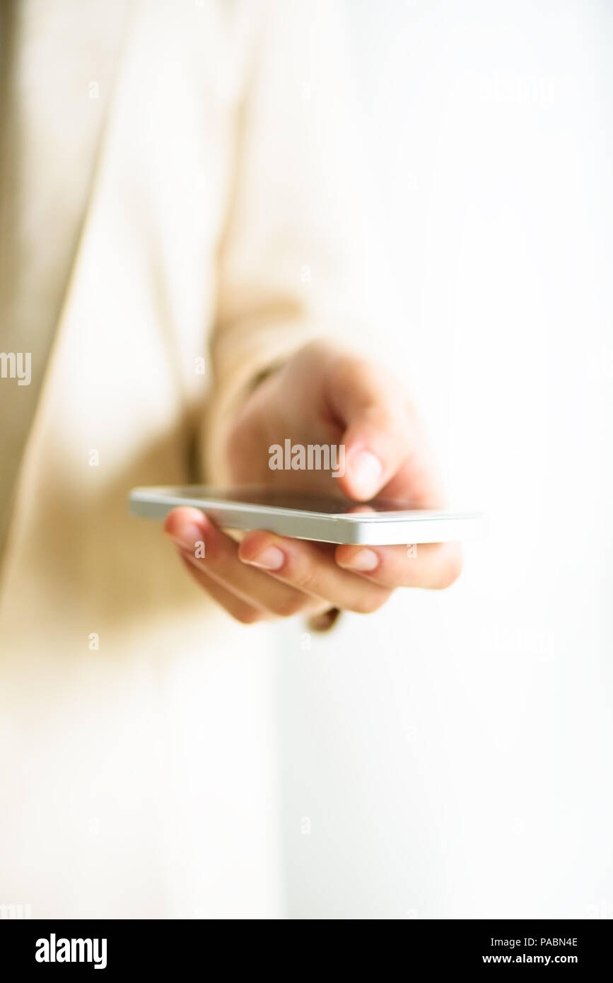 Woman hands hold cell phone on light cream background with copy space. Banner. Business, study, remote work, always connect concept. Smartphone - Stock Image