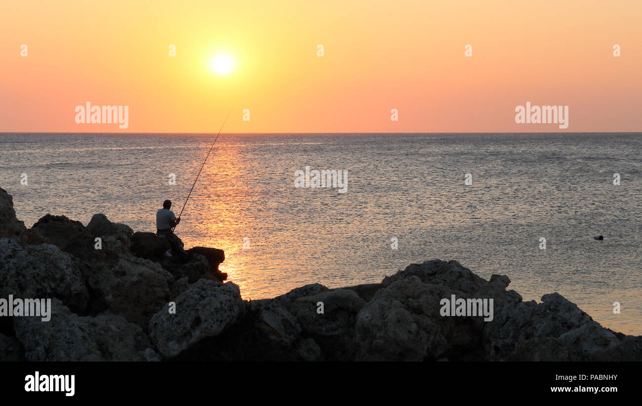 A lone angler on the rocks at Mandraki harbour in Rhodos, Greece at sunrise. - Stock Image