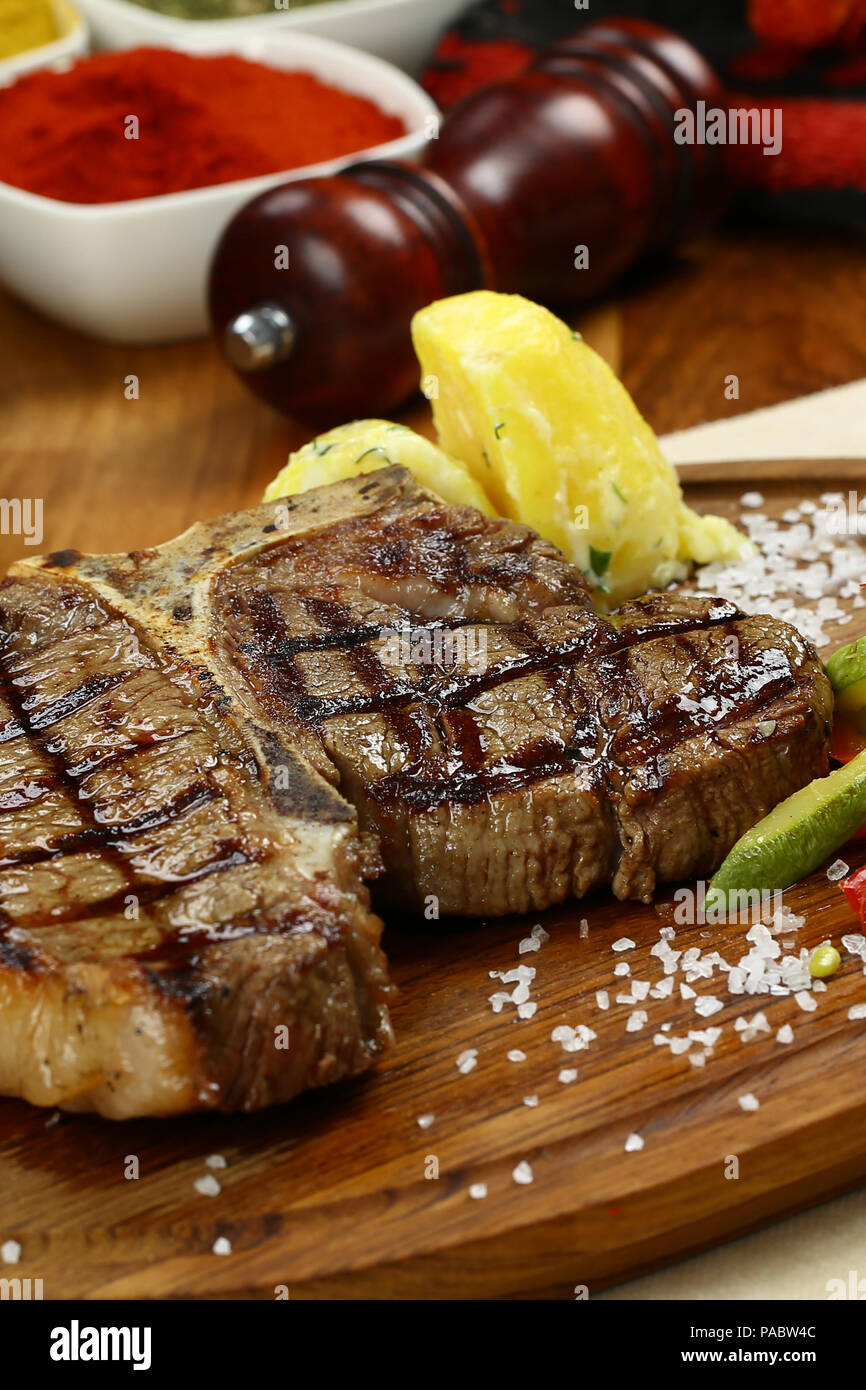 Roasted BBQ T-Bone Steak and herb butter on wooden cutting board Stock Photo