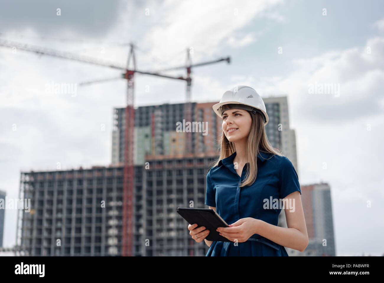 Female construction engineer. Architect with a tablet computer at a construction site. Young Woman looking, building site place on background. Construction concept - Stock Image