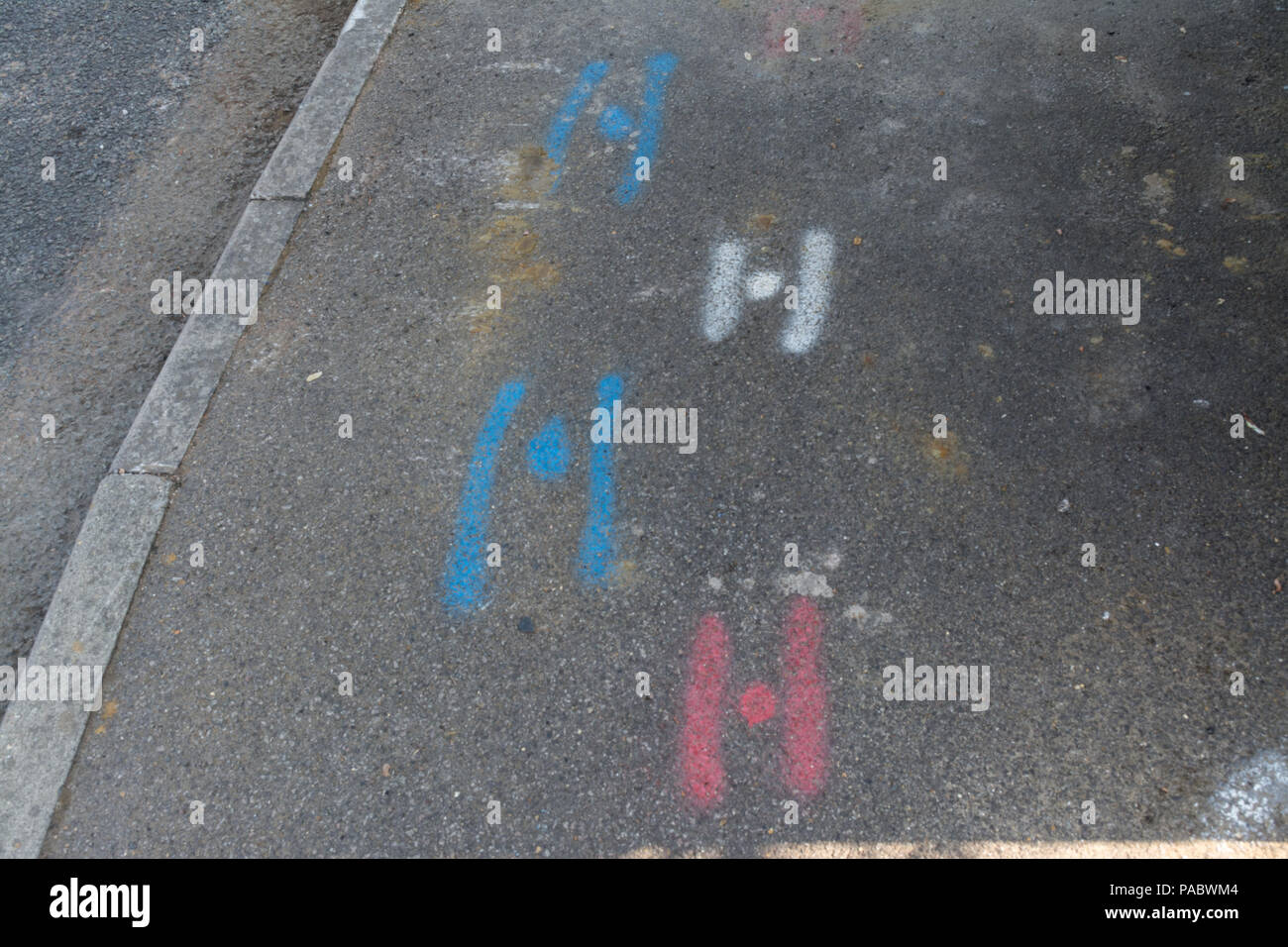 Spray painted markings squiggles on pavement made by contractors to indicate positioning of water, gas and electric utilities, pipes, cables - Stock Image