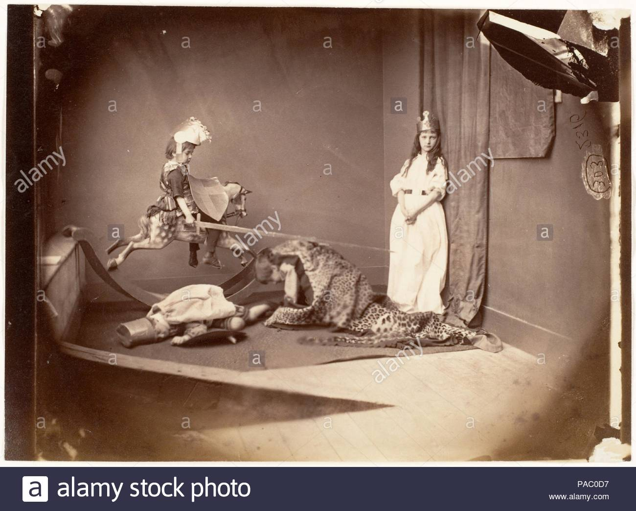 St. George and the Dragon. Artist: Lewis Carroll (British, Daresbury, Cheshire 1832-1898 Guildford). Dimensions: Image: 11.7 × 16 cm (4 5/8 × 6 5/16 in.). Date: June 26, 1875.  In 1872, Carroll had a studio built above his rooms at Christ Church so that he could make photographs even in inclement weather. With trunks full of toys and costumes from the Drury Lane Theatre, the 'glass house' was a paradise for children. Xie (Alexandra) Kitchin, a beautiful and photogenic child, was Carroll's muse in the 1870s. Born in 1864, she was the daughter of George William Kitchin, a colleague and an old fr - Stock Image