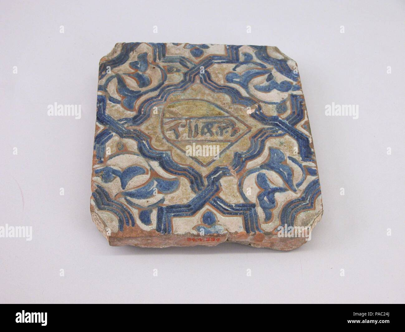Tile. Dimensions: H. 6 1/2 in. (16.5 cm)  W. 5 1/2 in. (14 cm)  D. 1 in. (2.5 cm). Date: second half 15th century.  So extravagant was the Alhambra palace that even some floors bore expensive ceramic tile. This tile probably comes from the Alhambra's Comares hall where fourteenth-century tiles were replaced in the late fifteenth century by new ones like this example, bearing similar designs but executed in cuerda seca. The tiles paving the hall today date to the sixteenth century. Museum: Metropolitan Museum of Art, New York, USA. Stock Photo