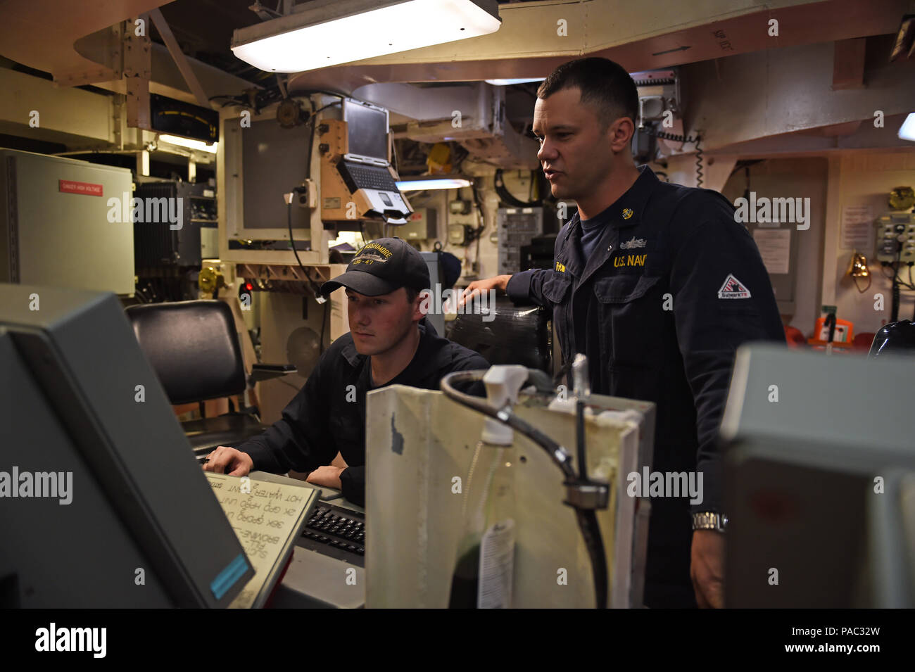160306-N-9263B-024 SAN DIEGO (Mar. 6, 2016) – Electrician's Mate Chief Jimmy Thomas (SW) trains Fireman (SW) Thomas Chappell on the propulsion and auxiliary control console, which was updated four years ago aboard the amphibious dock landing ship USS Rushmore (LSD 47). Rushmore is slated to begin more upgrades during the Chief of Naval Operation's planned maintenance availability period (PMA) at BAE Systems shipyard in San Diego, March 6. (U.S. Navy photo by Mass Communication Specialist 2nd Class Jason Baird/Released) - Stock Image