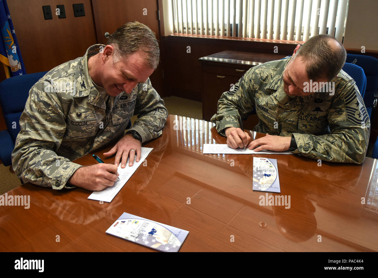 Col. Mark Slocum (left), 4th Fighter Wing commander, and Chief Master Sgt. Shane Wagner, 4th FW command chief, fill out donations slips for the 2016 Air Force Assistance Fund, March 3, 2016, at Seymour Johnson Air Force Base, N.C. The AFAF campaign began Feb. 29 and ends April 8 with a goal of raising $100,000. (U.S. Air Force photo/Airman Shawna L. Keyes) - Stock Image