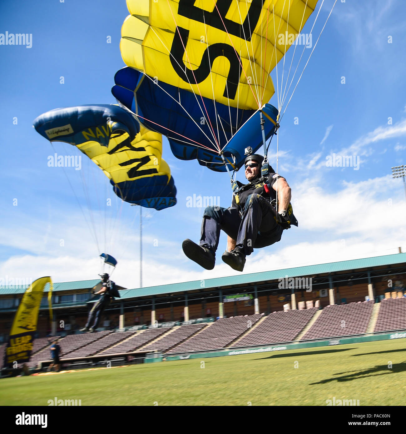 160304-N-VY375-089 LAKE ELSINORE, Calif. (March 4, 2016) Special Warfare Operator 1st Class Brandon Peterson, a member of the U.S. Navy parachute demonstration team the Leap Frogs, swoops in for a landing during a training demonstration at Storm Stadium, home of the Lake Elsinore Storm minor league baseball team. (U.S. Navy photo by Hospital Corspman 1st Class Shaun Thomas/Released) - Stock Image
