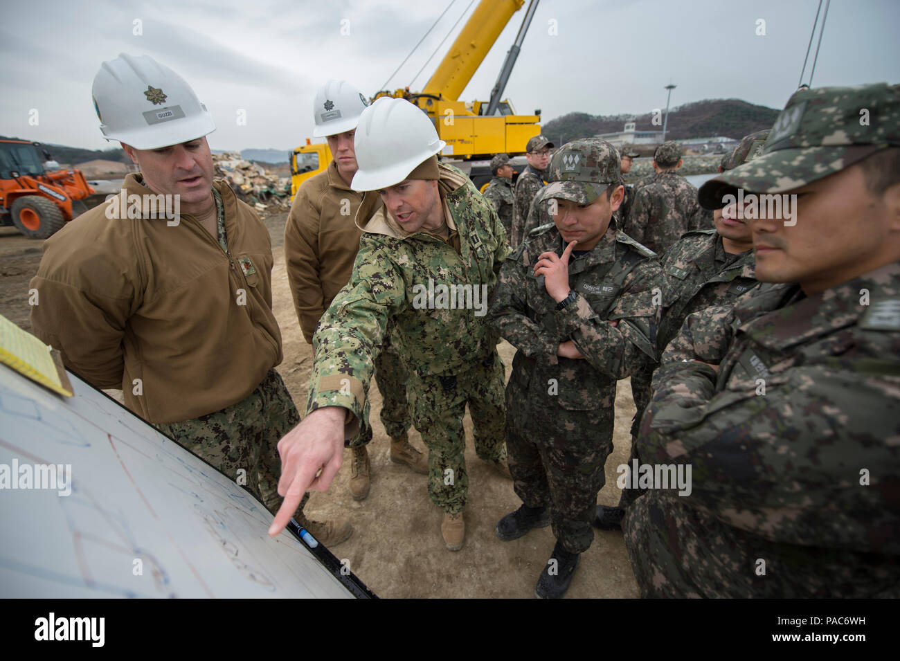 160308-N-HA376-048 JINHAE, Republic of Korea (March 8, 2016) - U.S. Navy Lt. Joshua Baker, executive officer of Underwater Construction Team (UCT) 2, briefs 30th Naval Construction Regiment and Republic of Korea (ROK) Seabees on a UCT 2 and ROK diver underwater project during exercise Foal Eagle 2016. The UCT 2 and ROK Seabee divers are working together to practice crane operations with divers in the water and underwater concrete block placement. Foal Eagle is an annual, bilateral training exercise designed to enhance the readiness of U.S. and ROK forces, and their ability to work together dur - Stock Image