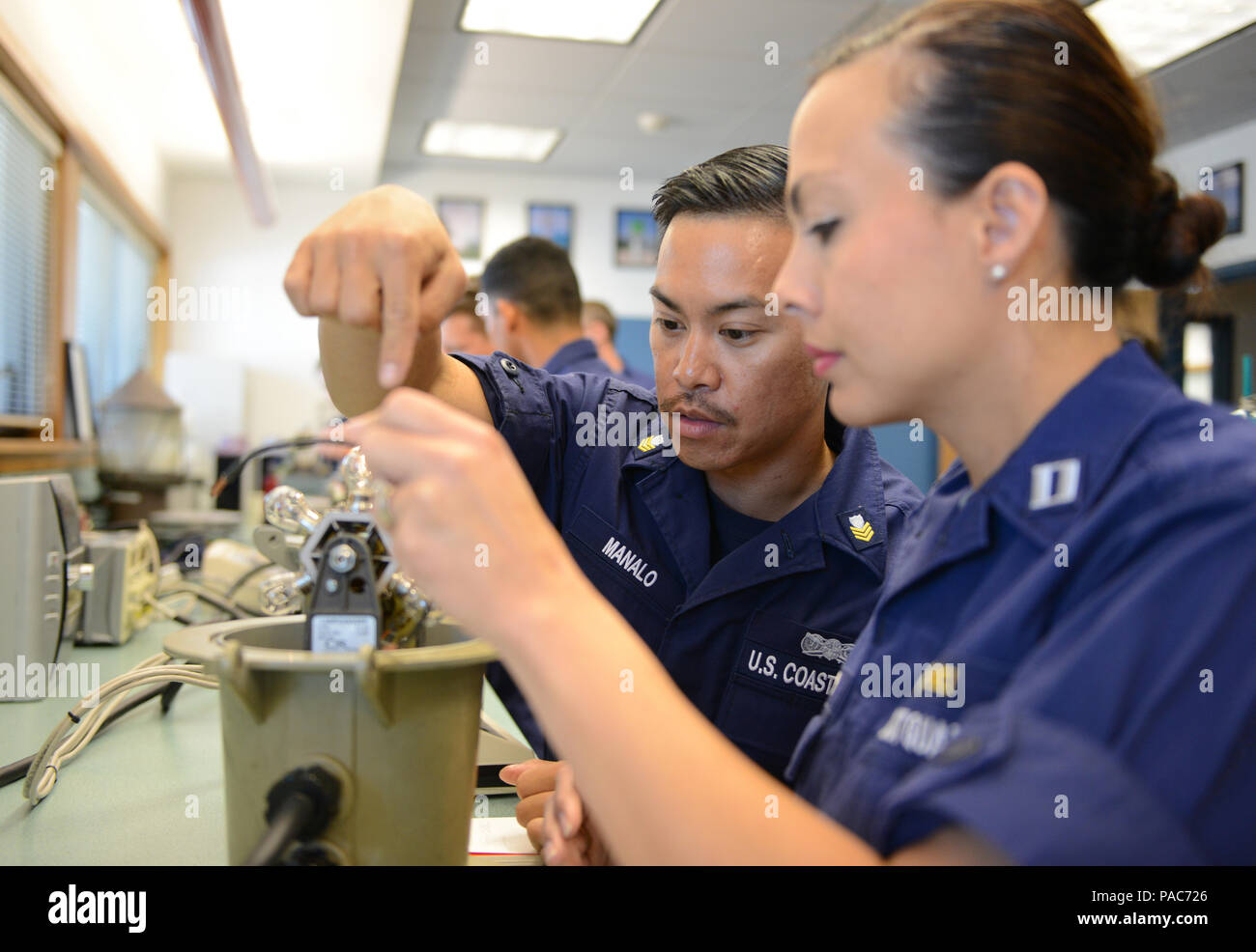 Lt. Furyisa Miller and Petty Officer 1st Class Michael Manalo, troubleshoot a light during a five-day minor aids to navigation maintenance training session for various units within the Coast Guard 14th District at Base Honolulu, March 9, 2016. Instructors from the Coast Guard 13th District conducted an overview of the ATON world providing instruction about buoys, structures, dayboards, lights and solar panels ensuring the members become efficient in their knowledge and capabilities to various aids they may work on in the field. (U.S. Coast Guard photos by Petty Officer 2nd Class Tara Molle/Rel - Stock Image