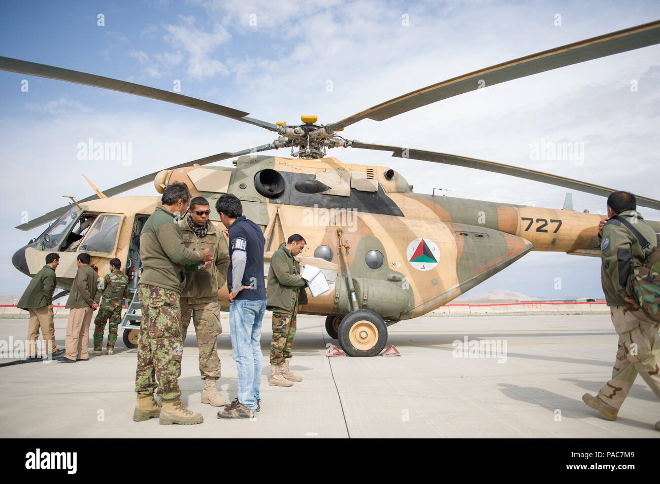 Tech. Sgt. Erik Edwards, Train Advise Assist Command - Air Mi-17 flightline advisor, talks with an Afghan Air Force member with the help of an interpreter near on the ramp at Kandahar Airfield, Afghanistan, March 2, 2016. As a functional command, TAAC-Air assists our Afghan partners to develop a professional, capable and sustainable force. (U.S. Air Force photo/Tech. Sgt. Robert Cloys) - Stock Image