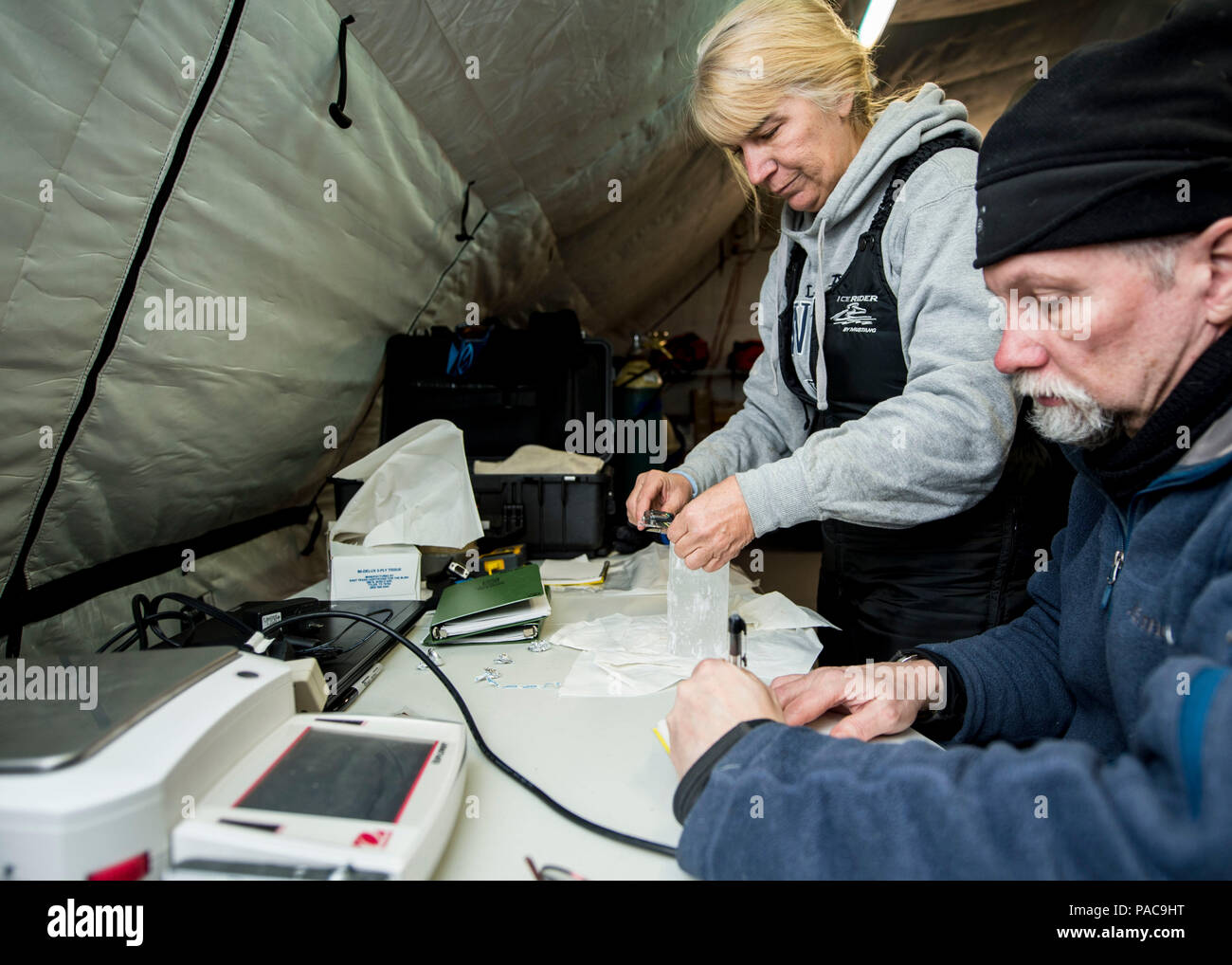 160310-N-QA919-502 ARCTIC CIRCLE (March 10, 2016) - Dr. Joan Gardener and Dr. Rick Hagen, with the Naval Research Lab, measure and weigh an ice core sample taken from the Arctic Circle during Ice Exercise 2016. The tests are part of an ongoing ice characterization research project. ICEX 2016 is a five-week exercise designed to research, test, and evaluate operational capabilities in the region. ICEX 2016 allows the U.S. Navy to assess operational readiness in the Arctic, increase experience in the region, advance understanding of the Arctic Environment, and develop partnerships and collaborati - Stock Image