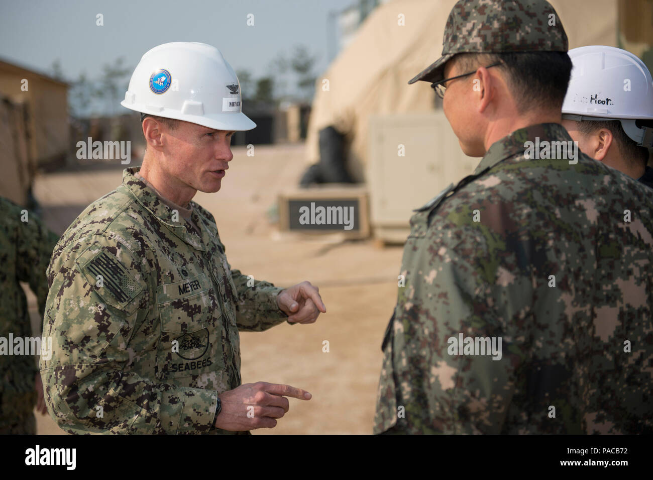 160314-N-HA376-039 BUSAN, Republic of Korea (March 14, 2016) - U.S. Navy Capt. James Meyer, commodore, 30th Naval Construction Regiment (30 NCR), speaks with Republic of Korea (ROK) Navy Cmdr. Lee Young Suk during a tour of a joint U.S. and ROK construction site during exercise Foal Eagle 2016. 30 NCR is forward deployed to provide command and control of U.S. Navy Seabees working with their ROK counterparts during Foal Eagle. Foal Eagle is an annual, bilateral training exercise designed to enhance the readiness of U.S. and ROK forces, and their ability to work together during a crisis. (U.S. N - Stock Image